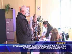 Председател на комисия дава на избиратели предварително попълнена бюлетина